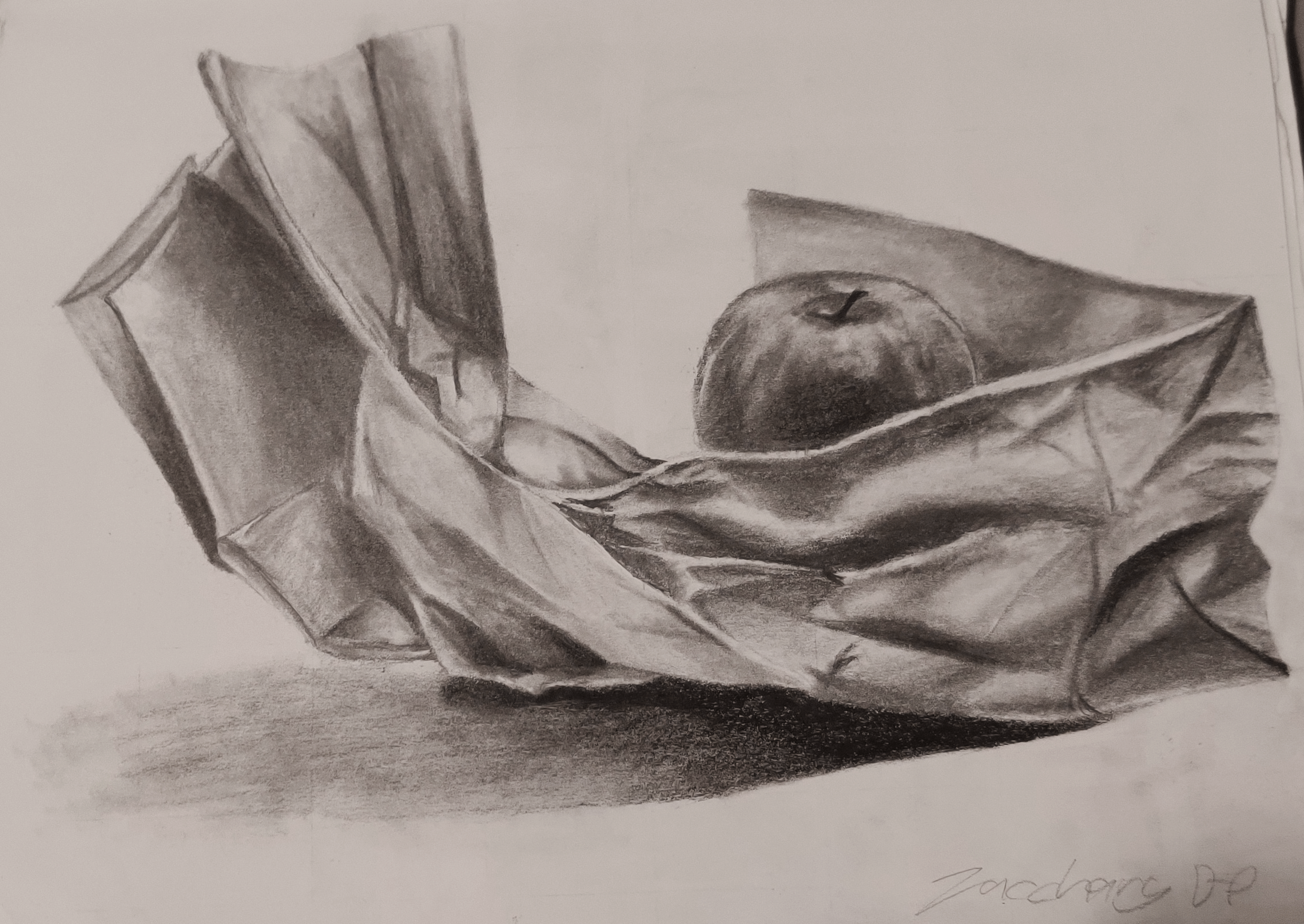 A value drawing of an apple resting on a paper bag.